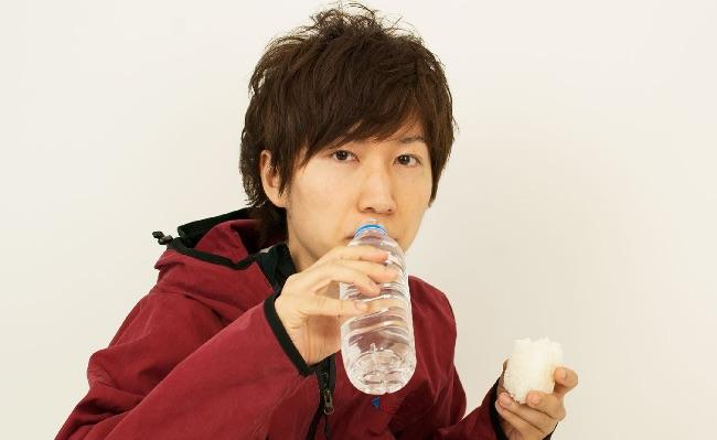 水とおにぎりを食べる男性