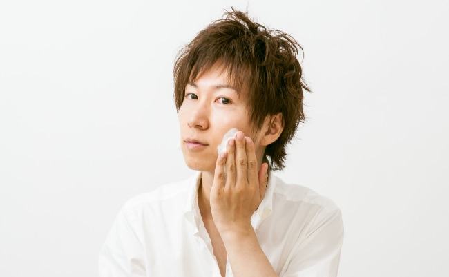 洗顔剤をつける男性