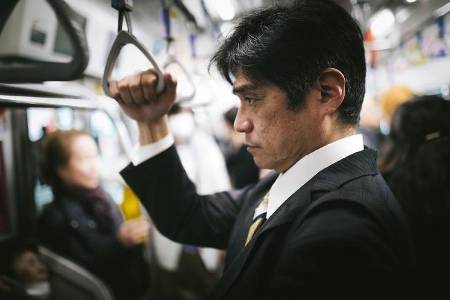 電車で帰宅する男性