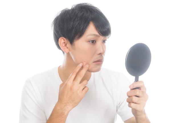 手鏡で自分の肌をチェックする男性