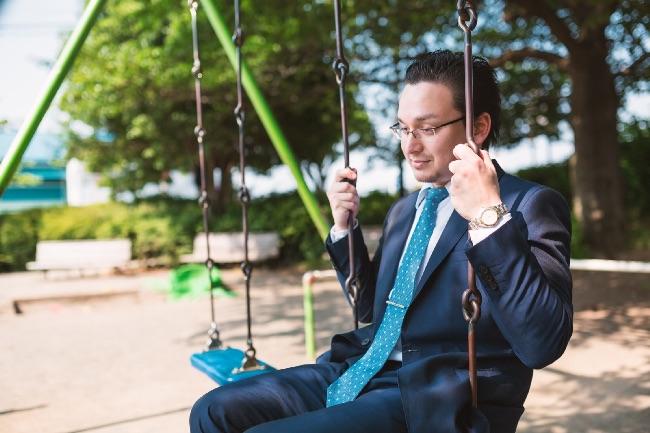 公園で1人ブランコに乗る男性