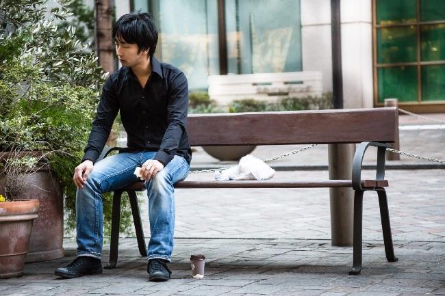 考え事をするベンチに座った男性